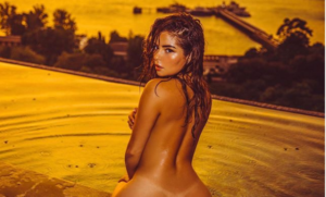 English model, Demi Rose shows off her exposed back side as she presents naked in new photographs